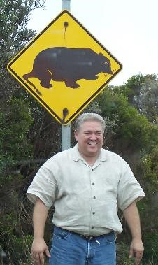 Dr. Garner standing next to Wombat crossing sign